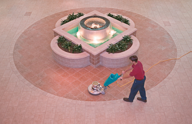 Man cleaning tiles near a fountain