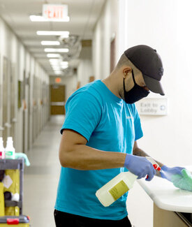 Man Wearing Face Mask Spraying Cleaner on Counter Surface & Wiping