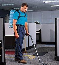 Man Cleaning Carpet Using Equipment