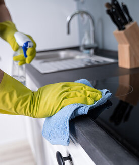 Hands wiping counter surface