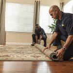 Man rolling up a carpet