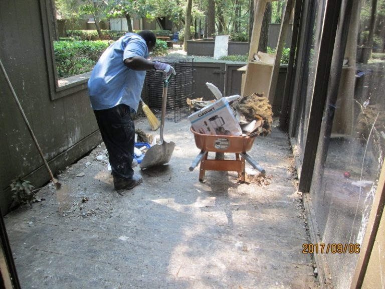 Man cleaning up debris with a shovel